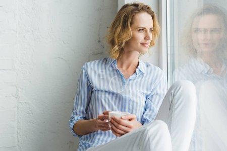 Photo pour Élégante jeune femme à la recherche dans la fenêtre et tenant la tasse de café - image libre de droit
