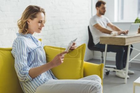 Photo pour Femme souriante avec homme taper sur ordinateur portable et tablette numérique - image libre de droit