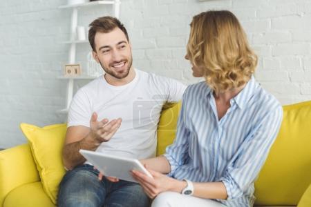 Photo pour Homme souriant parle copine avec tablette en mains - image libre de droit