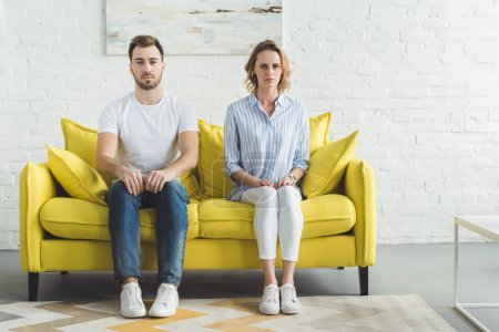 Photo for Young couple sitting on couch in front of brick wall with painting - Royalty Free Image