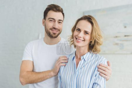 Young smiling man embracing girlfriend in room with painting on wall