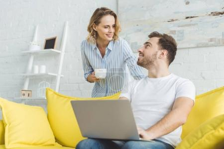 Man sitting in sofa with laptop and talking to girlfriend with cup in hand