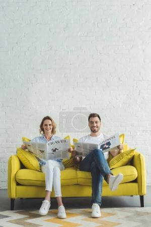 Young businessman with girlfriend sitting on sofa and reading newspaper about travel and business