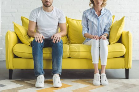Cropped image of young couple sitting on couch in modern room