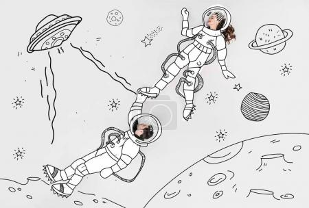 creative hand drawn collage with couple in space suits and ufo