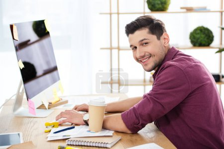 side view of smiling marketing manager working on computer at workplace in office