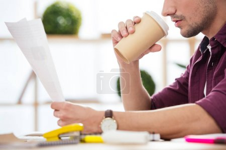 cropped shot of businessman with coffee to go doing paperwork at workplace in office