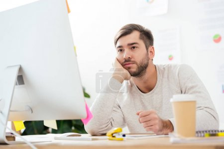 bored marketing manager looking at computer screen at workplace in office