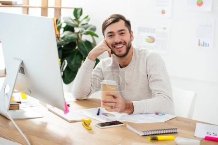 Photo for Portrait of smiling businessman with coffee to go at workplace in office - Royalty Free Image