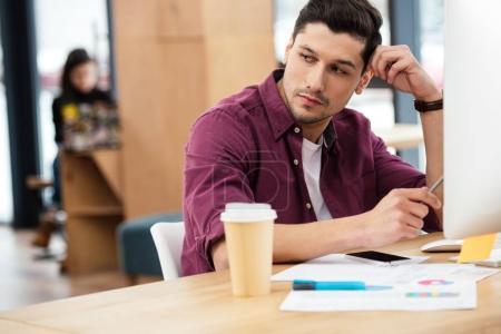 Photo pour Portrait d'homme d'affaires pensif regardant loin du milieu de travail avec café pour aller et papiers au bureau - image libre de droit