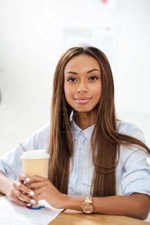 portrait of young smiling african american businesswoman with coffee to go in office