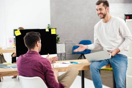 cheerful businessmen working at workplace together in office