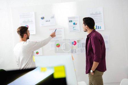 Photo pour Vue de jeunes entrepreneurs discutant la nouvelle stratégie de marketing dans le bureau arrière - image libre de droit