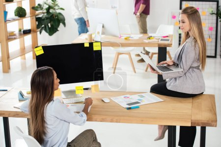 selective focus of multiethnic businesswomen at workplace and colleagues behind in office