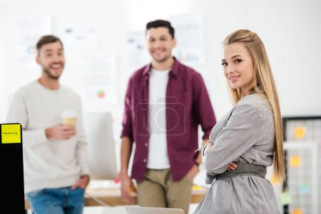 selective focus of smiling businesswoman looking at camera in office