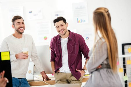 selective focus of smiling businessmen having conversation with businesswoman in office