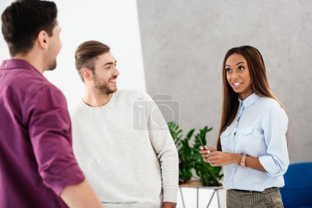Photo for Smiling multiethnic business colleagues having conversation in office - Royalty Free Image