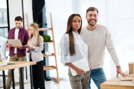 selective focus of smiling multiracial business people with colleagues behind in office
