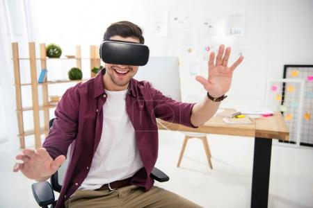 portrait of smiling marketing manager in virtual reality headset at workplace in office