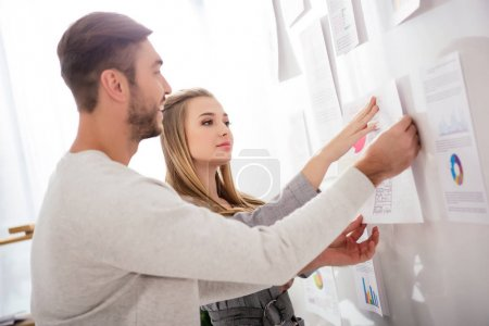 business colleagues putting document at white board with papers in office