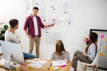 Photo pour Directeur du marketing pointant vers le tableau blanc avec des documents sur la réunion d'affaires avec des collègues multiethniques - image libre de droit