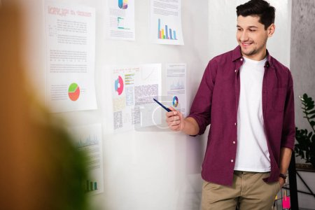 selective focus of smiling businessman pointing at white board with documents in office