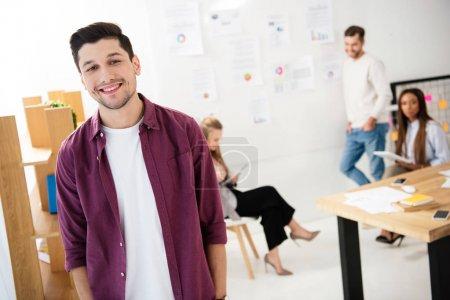Photo pour Mise au point sélective de responsable marketing souriant, regardant la caméra avec des collègues multiculturelles derrière au bureau - image libre de droit