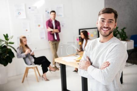 Photo pour Mise au point sélective de responsable marketing souriant, regardant la caméra avec des collègues multiculturelles derrière au bureau - image libre de droit
