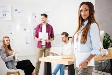 selective focus of smiling african american businesswoman looking at camera with multiethnic colleagues behind in office