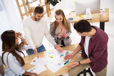 overhead view of multiethnic business colleagues discussing new marketing project at workplace in office
