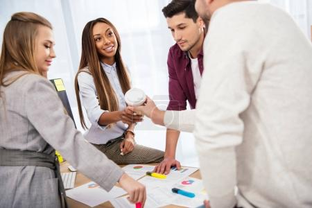 selective focus of businessman giving coffee to go to african american businesswoman during meeting with colleagues in office