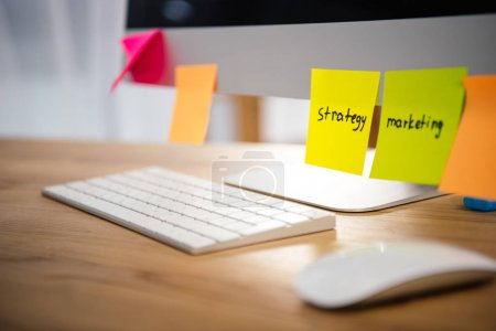 Photo for Close up view of colorful sticky notes with marketing and strategy lettering on computer screen at workplace - Royalty Free Image