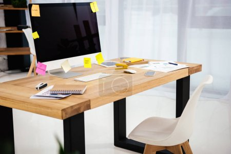 close up view of workplace with blank computer screen, sticky notes and documents in office