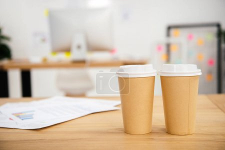 close up view of disposable cups of coffee at workplace with papers in office