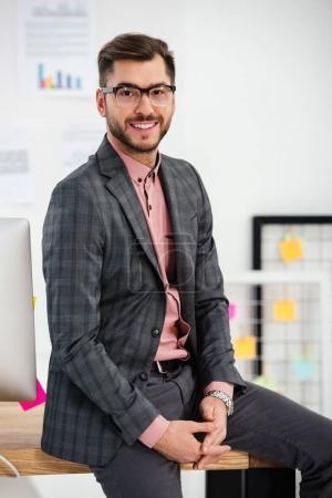 retrato de hombre de negocios sonriente en traje y anteojos sentado en la mesa y mirando a la cámara en la oficina