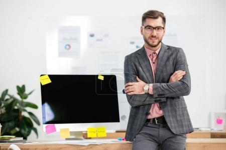 portrait of businessman in suit and eyeglasses standing at workplace with blank computer screen in office