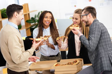 portrait of multiethnic business people eating pizza together in office