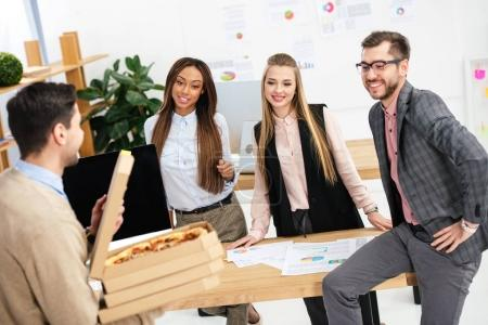 selective focus of businessman brought pizza for multiethnic colleagues in office