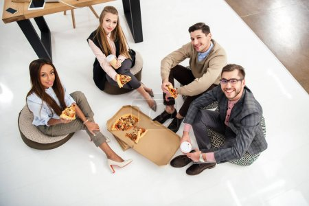 high angle view of smiling multiethnic business people with pizza looking at camera in office