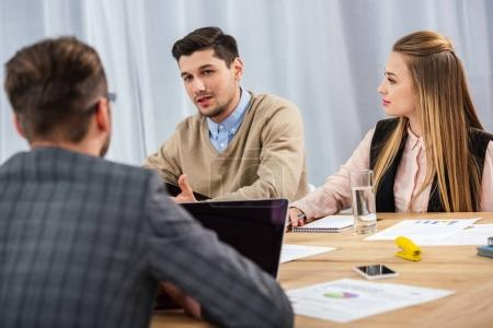 partial view of young business people at workplace during business meeting in office
