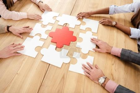Photo for Partial view of multiracial business people collecting blank puzzles at wooden table, teamwork concept - Royalty Free Image