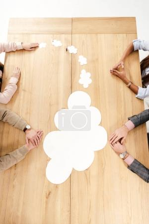 overhead view of multiracial business people at wooden table with empty paper clouds, teamwork concept