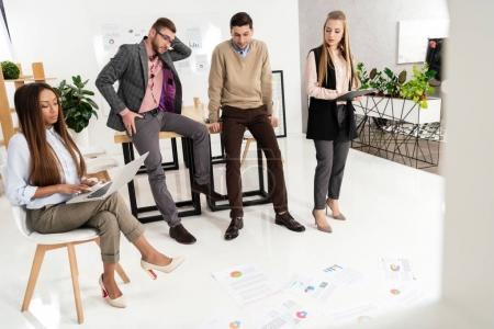 multicultural group of marketing managers looking at papers arranged on floor in office