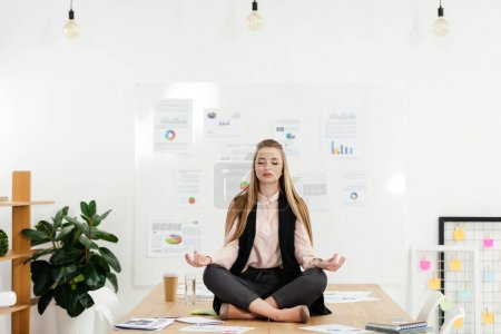 Photo for Calm businesswoman meditating in lotus position on table in office - Royalty Free Image