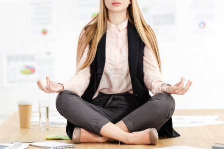 cropped shot of businesswoman meditating in lotus position on table in office