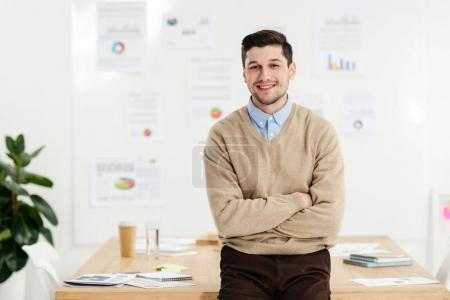 portrait of smiling marketing manager with arms crossed leaning on workplace in office