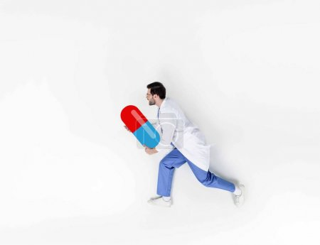 creative collage of handsome young doctor running and holding drawn pill