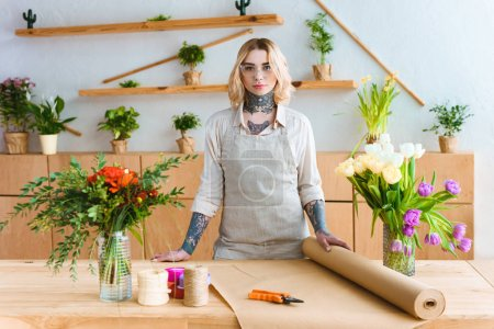 beautiful young florist in apron and eyeglasses standing at workplace and looking at camera
