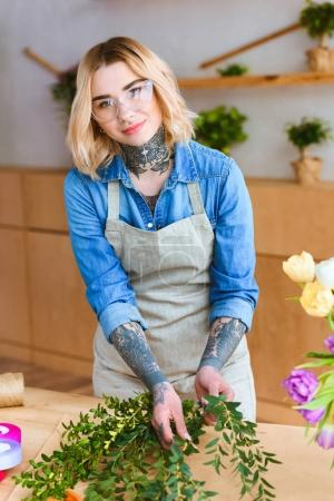 beautiful young florist in eyeglasses arranging plants and smiling at camera in flower shop