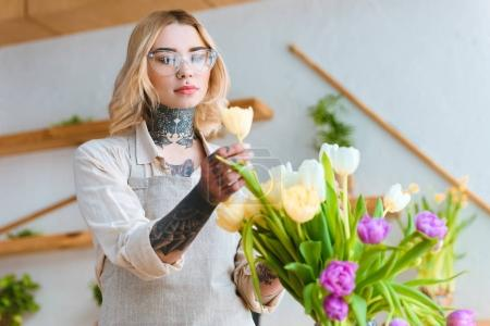 young female florist in eyeglasses working with beautiful tulips